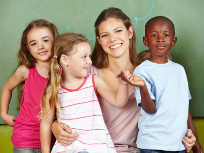 28578600-happy-woman-with-three-different-children-in-a-kindergarten