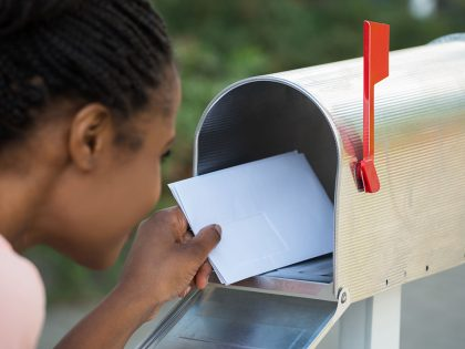 48628166-close-up-of-woman-putting-letter-in-mailbox